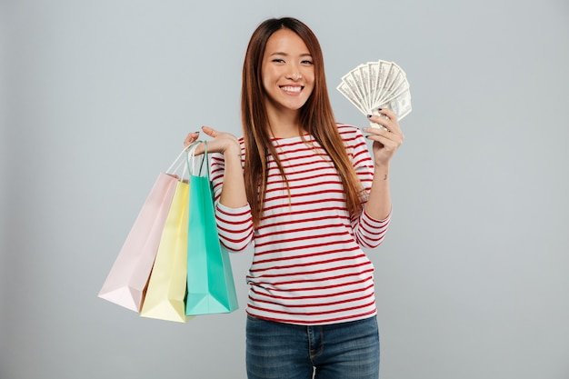 Heureuse femme asiatique en pull tenant de l'argent et des colis