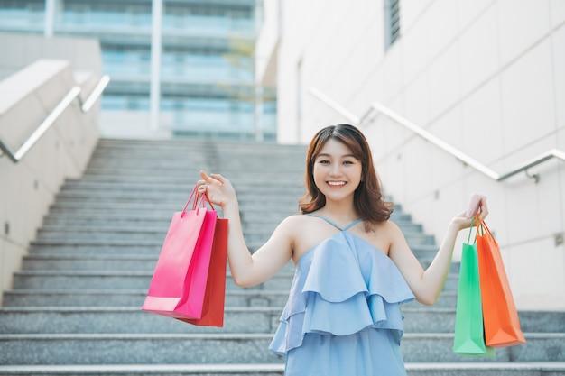 Heureuse femme asiatique qui descend avec de nombreux sacs à provisions colorés.
