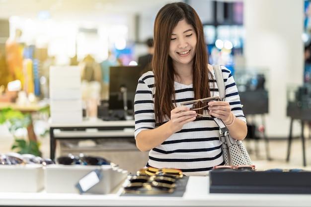 Heureuse femme asiatique à la recherche et essayer les lunettes en magasin magasin au grand magasin