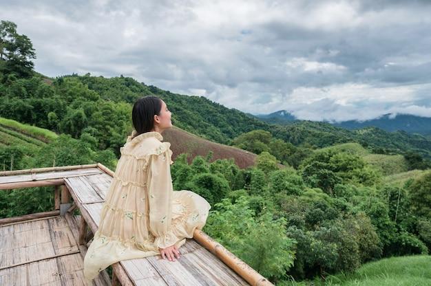 Heureuse femme asiatique en robe jaune assise sur une terrasse en bois parmi la montagne en vacances