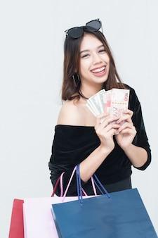Heureuse femme asiatique avec sac à provisions et avoir de l'argent