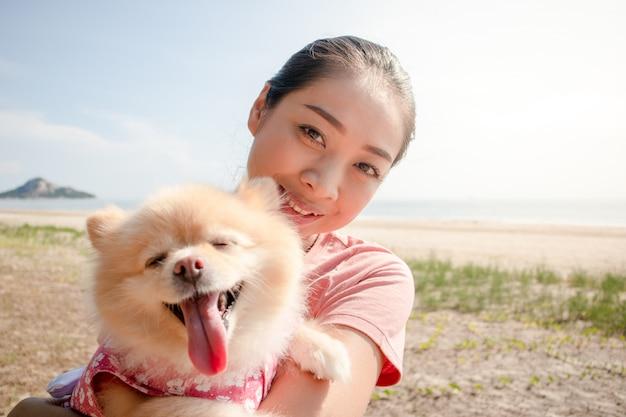 Heureuse femme asiatique avec son chiot poméranien.
