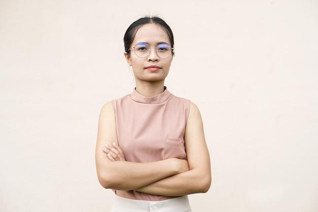 Heureuse femme asiatique souriante fond de mur gris