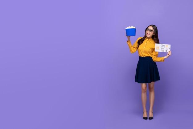 Heureuse femme asiatique souriante avec des lunettes 3d pop-corn et billet de cinéma