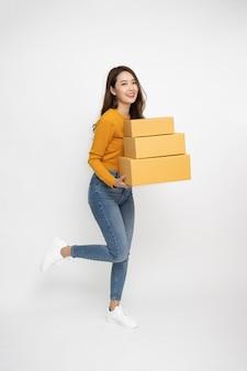 Heureuse femme asiatique souriante et tenant une boîte à colis isolée sur fond blanc, concept de service de messagerie et d'expédition, composition de personnes pleine longueur