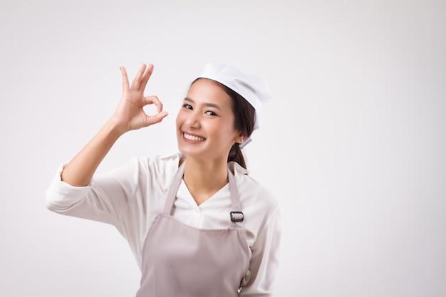 Heureuse femme asiatique souriante travailleuse domestique pointant le geste de la main ok