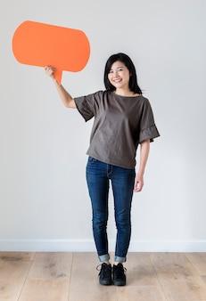 Heureuse femme asiatique tenant bulle de dialogue fond