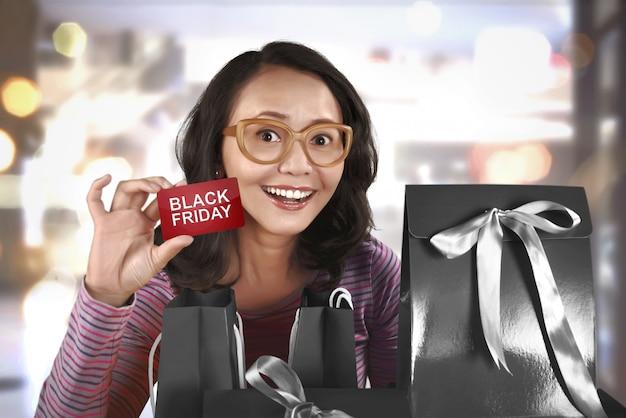 Heureuse femme asiatique tenant carte avec black friday
