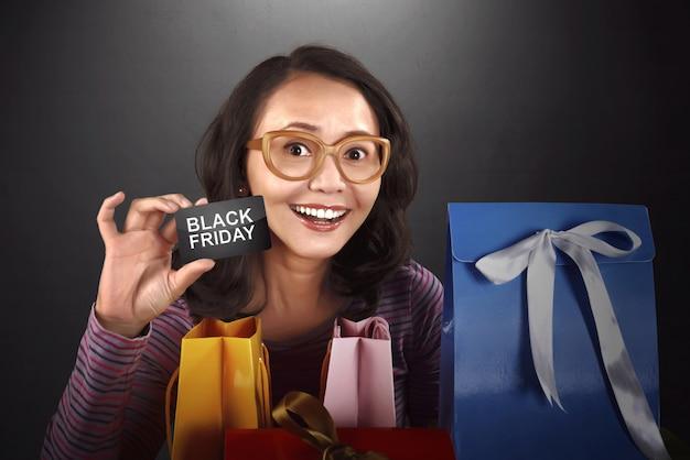 Heureuse femme asiatique tenant carte avec texte black friday