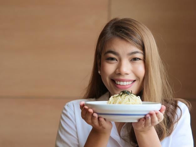 Heureuse femme asiatique tenant des nouilles dans les mains au restaurant, concept de temps de déjeuner.