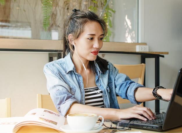 Heureuse femme asiatique travaillant dans un café.