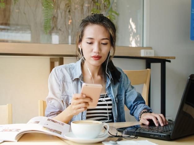 Heureuse femme asiatique travaillant et utiliser un téléphone intelligent dans un café