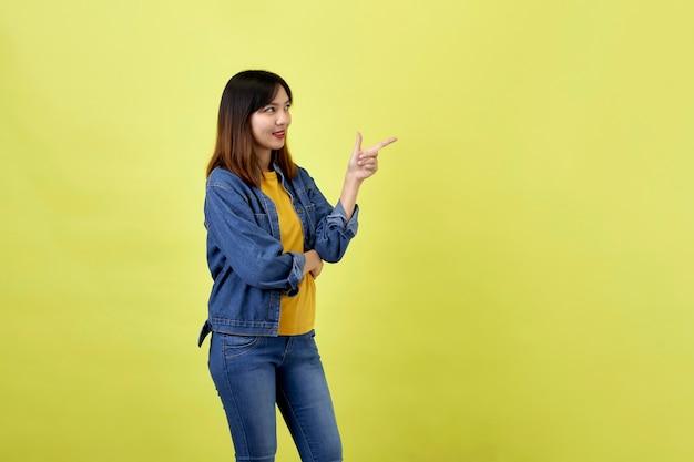 Heureuse femme asiatique en veste en jean côté pointant pour copier l'espace et en regardant la caméra sur l'espace jaune