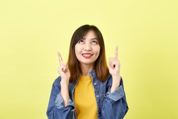 Heureuse femme asiatique en veste en jean pointant vers le haut pour copier l'espace et en regardant la caméra sur l'espace jaune