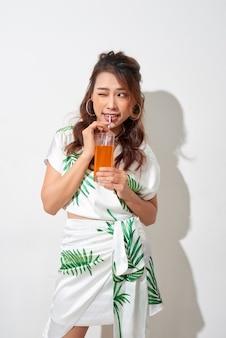Heureuse femme asiatique en vêtements décontractés d'été avec un verre de boisson de jus de fruits frais