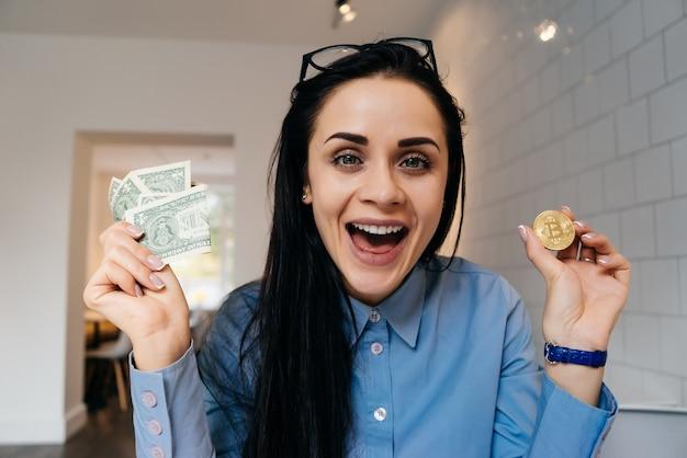 Heureuse femme assise au bureau et tenant une crypto-monnaie