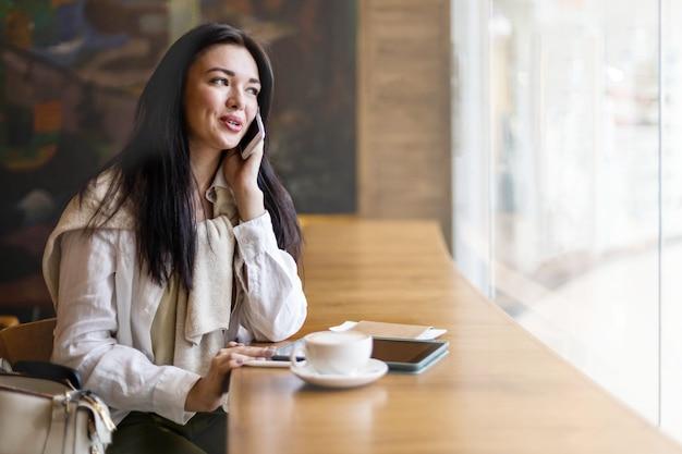 Heureuse femme assise au café en attente de vol de départ dans le terminal de l'aéroport parlant utiliser un smartphone