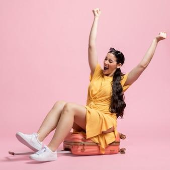 Heureuse femme assise sur les bagages