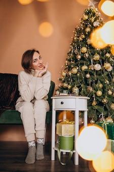 Heureuse femme assise sur un canapé près de l'arbre de noël