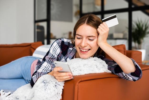 Heureuse femme assise sur le canapé en regardant téléphone