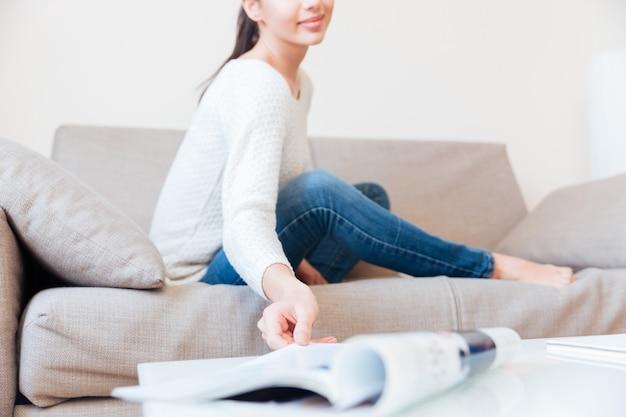 Heureuse femme assise sur le canapé
