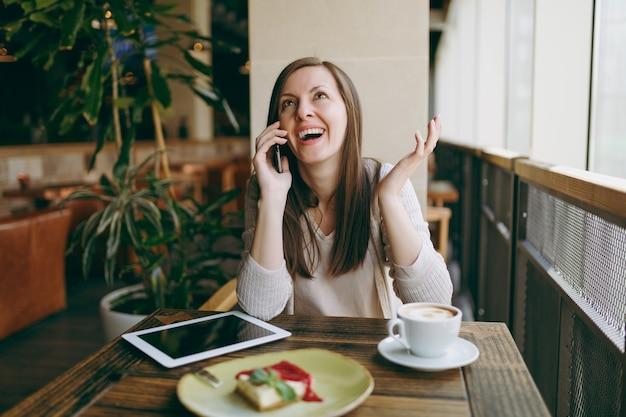 Heureuse femme assise dans un café avec une tasse de cappuccino, un gâteau, parlant au téléphone portable, se relaxant au restaurant pendant le temps libre. femme travaillant sur ordinateur tablette pc reste au café. concept de mode de vie.