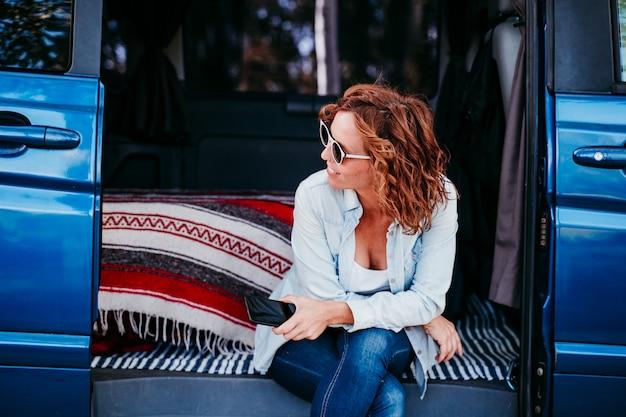 Heureuse femme assise dans une camionnette bleue et s'amuser. concept de voyage. femme à l'aide de téléphone portable
