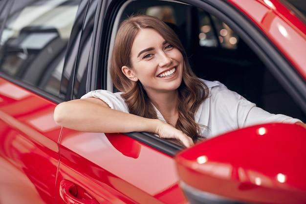 Heureuse femme assise dans une nouvelle automobile