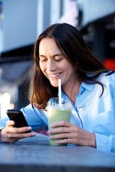 Heureuse femme assise à l'extérieur avec du jus et regardant le téléphone mobile