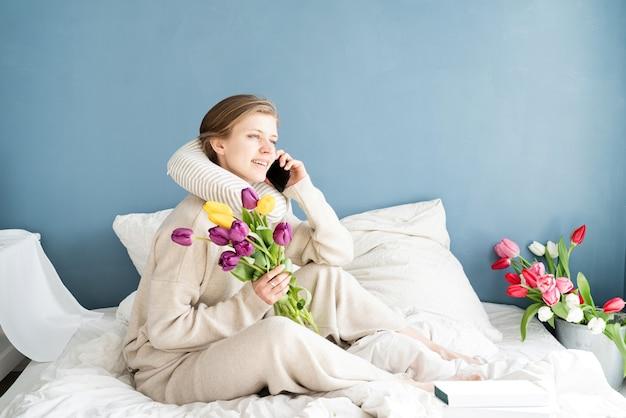 Heureuse femme assise sur le lit en pyjama parler au téléphone, fond de mur bleu