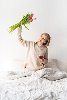 Heureuse femme assise sur le lit en pyjama, avec plaisir en appréciant des fleurs et un verre de vin rouge