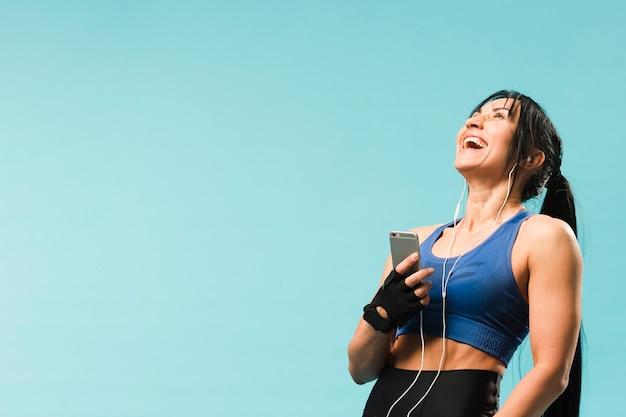 Heureuse femme athlétique appréciant la musique dans les écouteurs