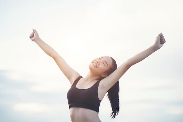 Heureuse femme athlétique souriante avec les bras tendus