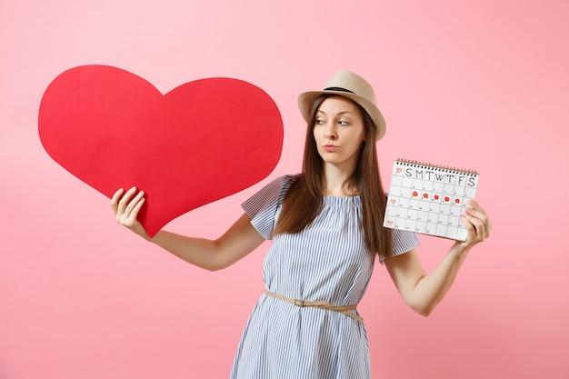 Heureuse femme au chapeau d'été en robe bleue tenant un grand coeur rouge vide vide, calendrier des périodes féminines, vérifiant les jours de menstruation isolés sur fond. concept gynécologique de soins médicaux. espace de copie