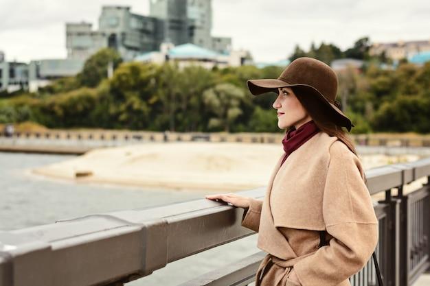 Heureuse femme au chapeau marron et manteau beige se tient au bord du remblai et regarde dans le lointain.