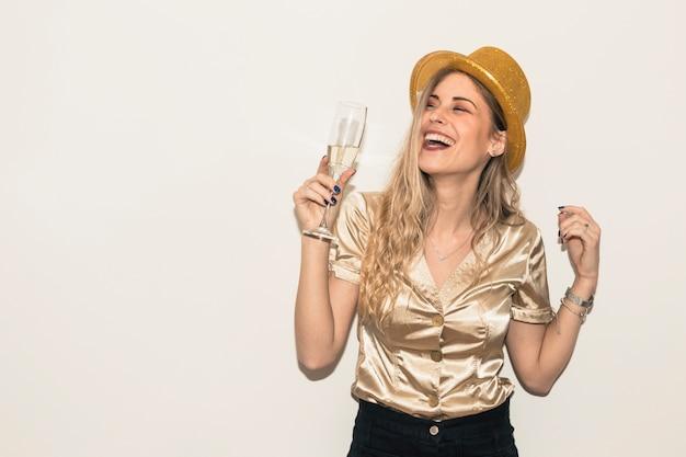 Heureuse femme au chapeau avec verre de champagne