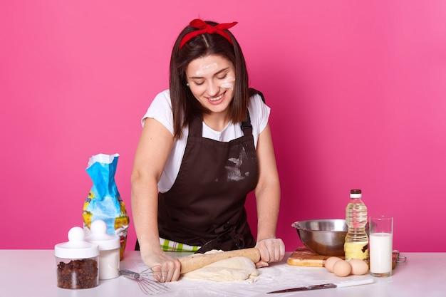 Heureuse femme au foyer ou boulanger détient le rouleau à pâtisserie et déroule la pâte avec une expression faciale appréciée