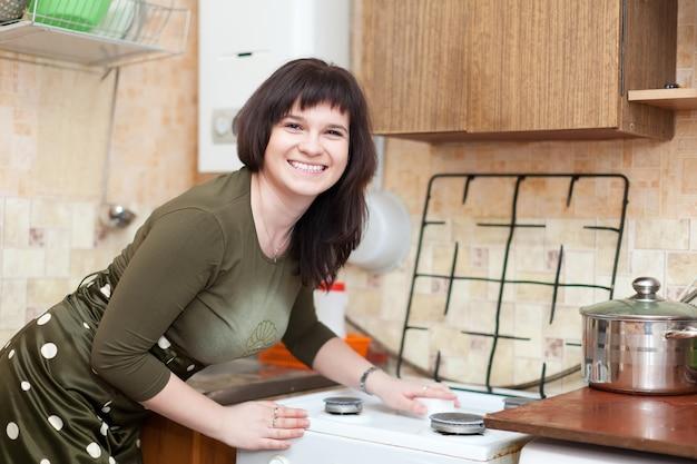 Heureuse femme au foyer nettoie la cuisinière à gaz avec une éponge de mélamine