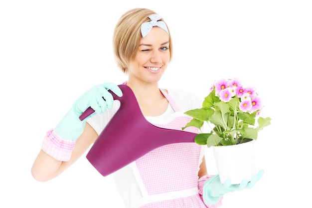 Une heureuse femme au foyer rétro arrosant des fleurs sur fond blanc