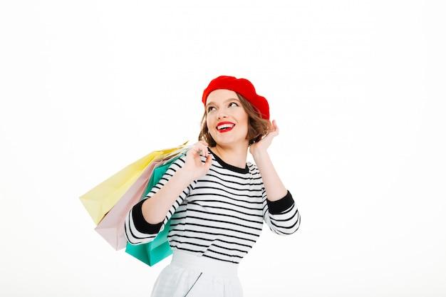 Heureuse femme au gingembre avec des paquets corrige sa coiffure et regarde au-dessus du gris