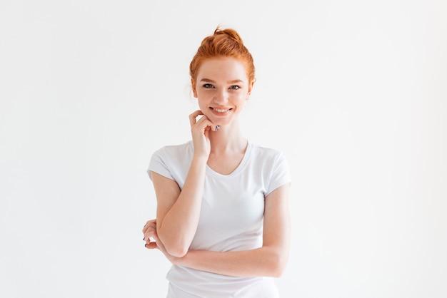 Heureuse femme au gingembre en t-shirt avec la main près du visage à la recherche
