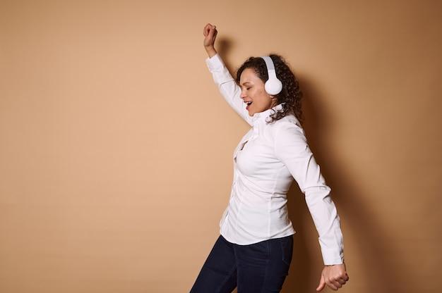 Heureuse femme aux cheveux bouclés dansant avec les bras tendus sur un mur beige tout en écoutant de la musique au casque. copier l'espace
