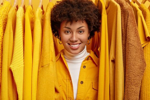 Heureuse femme aux cheveux bouclés souriante cherche quoi porter, se tient entre des tenues lumineuses