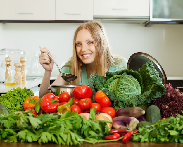 Heureuse femme aux cheveux longs, cuisiner avec des tas de légumes