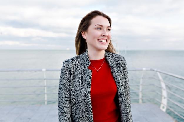 Heureuse femme aux cheveux longs souriante avec de grands yeux bleus en chemise rouge et manteau gris se promène près de la mer