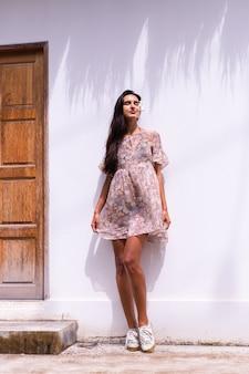 Heureuse femme aux cheveux longs souriante en robe se dresse sur le mur blanc