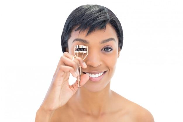 Heureuse femme aux cheveux noire à l'aide d'un recourbe-cils