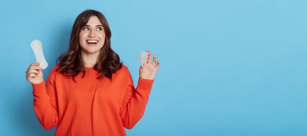 Heureuse femme aux cheveux noirs excitée à la recherche de suite avec un sourire à pleines dents