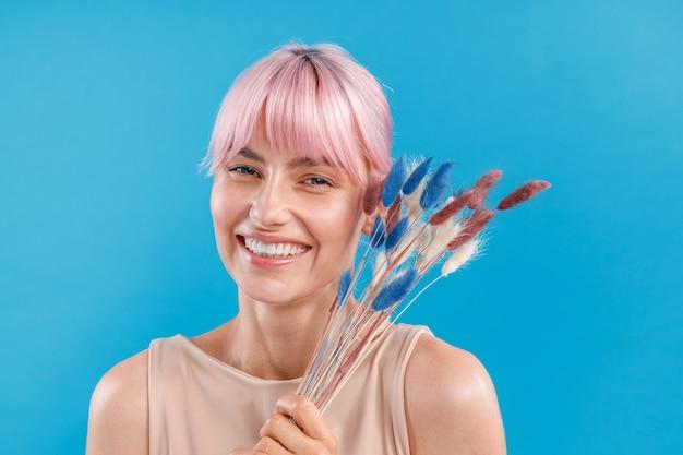 Heureuse femme aux cheveux roses souriant à la caméra tenant de l'herbe de la pampa séchée dans sa main posant sur bleu