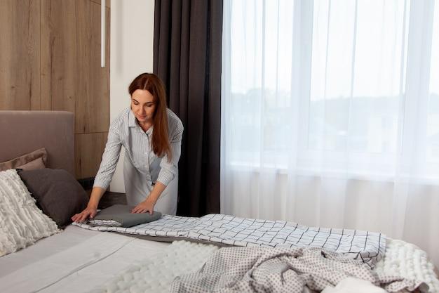 Heureuse femme aux longs cheveux roux est un ensemble de literie pliant sur le lit de la chambre avec espace de copie. fabrication textile biologique. le linge est décoré de rayures en forme de cage. différents oreillers